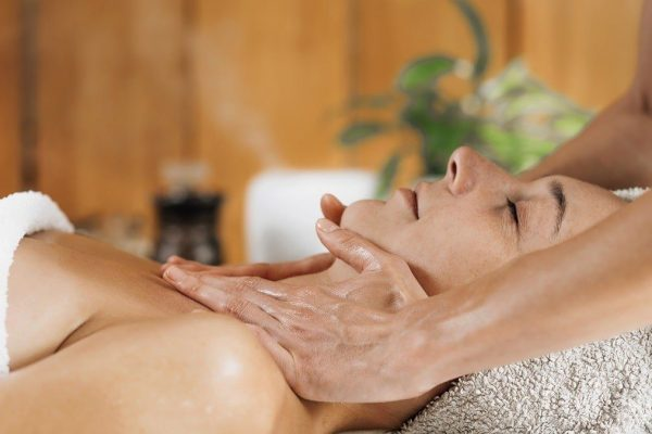 Woman enjoying professional Ayurveda neck and shoulders massage with ethereal oil
